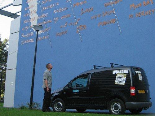 Kunstwerk Marieken Verheyen op Bijlmerflat Amsterdam, werelddelen als muurschildering, meridianen in neon en tekst gefreesd, artwork, mural