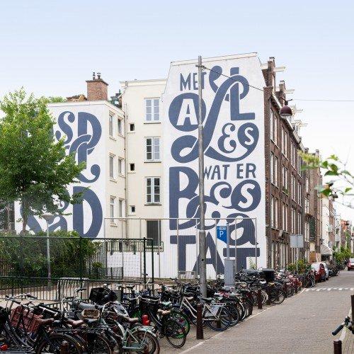 Kunstwerk Piet Parra voor school in Amsterdam, uitgevoerd door Iwaarden als muurschildering op een gevel aan het schoolplein
