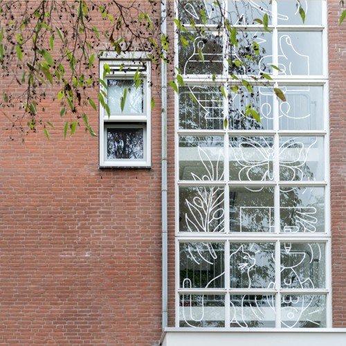 Illustraties van kunstenaar Gino Bud Hoiting in folie op ramen van woningen Almere